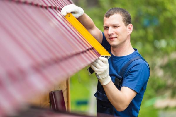 Worker Taking Measurement Of Roof