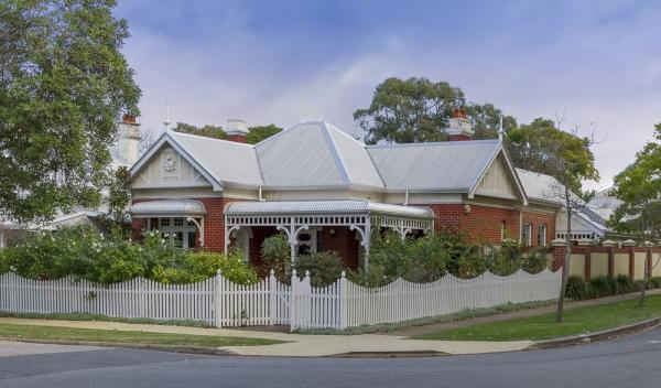 House With Matching White Roof And White Picket Fence