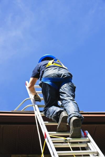 Worker With Safety Harness Climbing To The Roof
