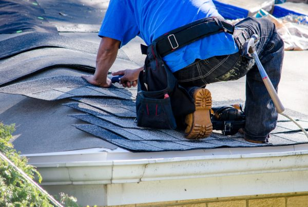 A worker replaces tiles on the roof of a home