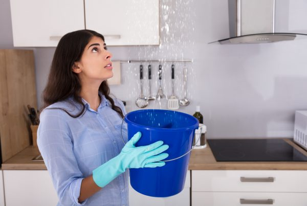 Worried Woman Holding Bucket While Water Droplets Leak From Ceiling In Kitchen