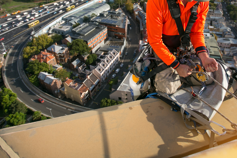 Working caring for commercial roof using abseiling equipment.